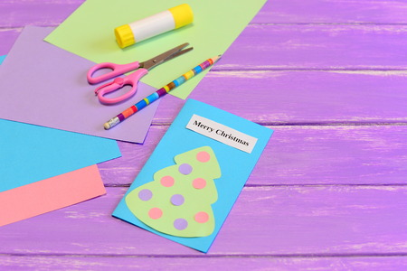 How to create simple Christmas card crafts for kids. Tutorial. Colored paper pieces, scissors, pencil, glue stick, greeting card Merry Christmas on lilac wooden background. Holiday children activity 版權商用圖片