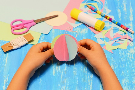 Kid holds a paper Christmas tree ball in his hands. Kid shows Christmas paper crafts. Scissors, pencil, glue stick, colored paper pieces and scraps on blue wooden background. Children holiday crafts Stock Photo