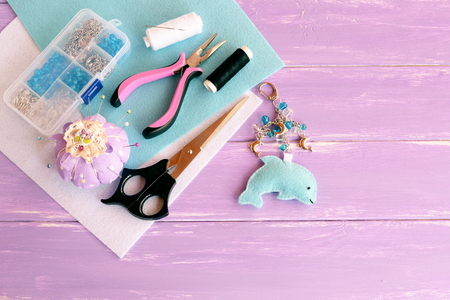 Cute felt dolphin with beads. Handmade felt keychain for bag charm. Easy kids summer crafts. Beads, thread, needle, scissors, pliers, pincushion, pins. Wooden background. Crafts supplies and tools
