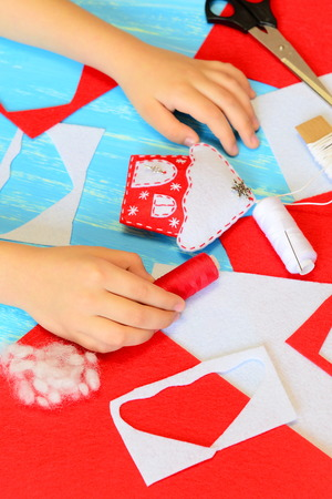 card making: Child making Christmas crafts. Child put his hands on a table. Colorful felt house ornament. Materials and tools for creating Christmas tree ornaments. Children handcraft concept