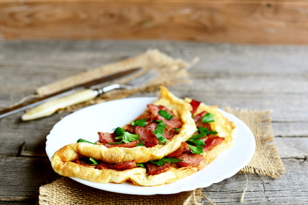 Delicious bacon omelette on a plate. Homemade folded omelette with fried bacon decorated with parsley. Hearty eggs breakfast recipe. Fork, knife, burlap textile on a wooden table. Rustic cuisine