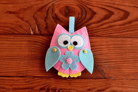 Felt owl embellishment. Felt owl embellishment. Felt owl toy. How to make a cute felt owl - kids DIY crafts tutorial. Wooden table. Hand sewing guide. Sewing instructions step by step. Basic sewing 版權商用圖片