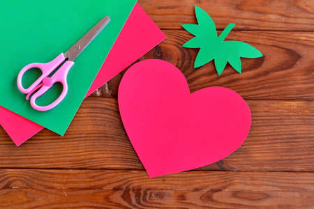 Paper red heart, paper green leaves on a wooden table. Paper red heart, paper green leaves on a wooden table. Paper pattern. Paper sheets, scissors - set for children's art. Kids crafts. DIY concept 版權商用圖片