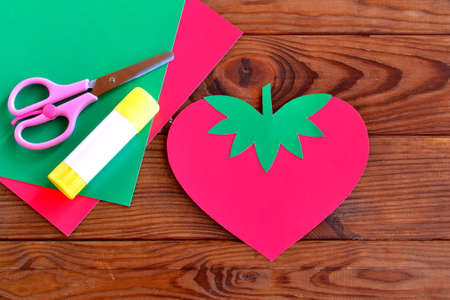 Set for children's art. Paper strawberry, paper sheets, scissors, glue - set for children's art. Kids crafts. DIY concept. Brown wooden table. Strawberry paper crafts for kids. Strawberry cards diy