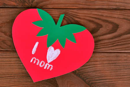 Greeting card with text I love mom. Gift for mother on birthday, March 8, mother's day, Valentine's day. Wooden table. Children crafts, greeting card I love mom. Paper strawberry. Original postcard