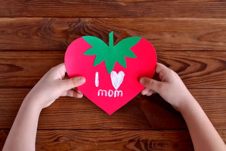 Child holds greeting card in his hands. Child holds greeting card in his hands. Paper card strawberry. Greeting card mother's day. Valentine's day greeting card. Womens day greeting card for 8 march