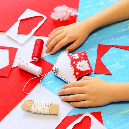 Kind machte einen Filz Weihnachtsbaum Hausdekoration. Kinderweihnachtsshow Hausdekoration. Werkzeuge und Materialien für das Nähen Handwerk. Einfache Winter handgemachte DIY für Kinder. Blaue hölzernen Hintergrund Standard-Bild