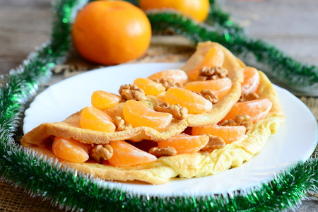 Sugary omelet on a plate. Homemade fried omelet stuffed with fresh mandarins and raw walnuts, green garland, fresh mandarins on old wooden table. Christmas breakfast omelette recipe. Closeup