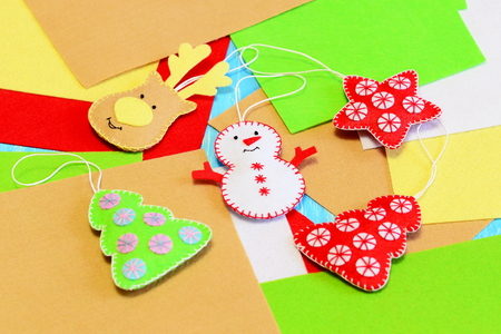 Homemade Christmas tree ornaments crafts. Adorable felt deer, Christmas tree, snowman, star ornaments on colored felt background. Christmas handmade crafts and activities for children. Closeup 版權商用圖片