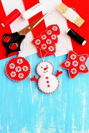 Cute Christmas tree embellishment. Felt snowman, Christmas tree, star and ball embellishment, materials and tools for sewing on wood background with copy space for text. Christmas kids DIY background 版權商用圖片