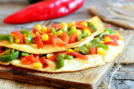 Stuffed omelet on a wooden board. Healthy fried omelet stuffed with red and green bell peppers and corn. Easy vegetarian breakfast omelet recipe. Rustic style. Closeup Stock Photo