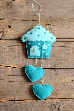 wall decor: Felt house with hearts decor isolated on old wooden background. Handmade home wall decor. Felt wall decoration crafts for Christmas, Valentines day, mothers day. Closeup. Top view