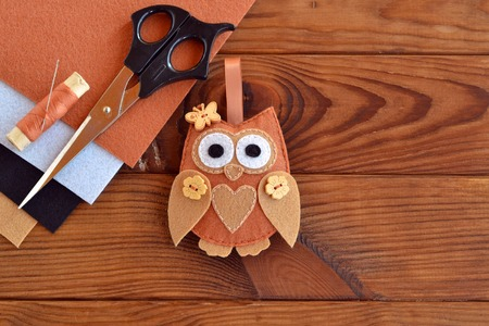 Felt brown owl toy. Shabby chic style. Kids crafts. Scissors, thread, needles, felt sheets - sewing kit. Brown wooden table Stock Photo