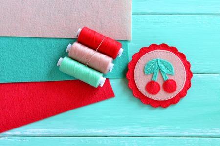 Felt brooch hand embroidered summer. Beautiful handmade felt brooch. Idea of ??childrens art. Felt cherry ornament. Kids craft idea Stock Photo