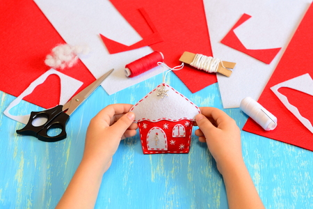 Little kid made a Christmas tree house ornament of red and white felt. Child holds Christmas house ornament in his hands. Tools and materials for making craft projects. Blue wooden background
