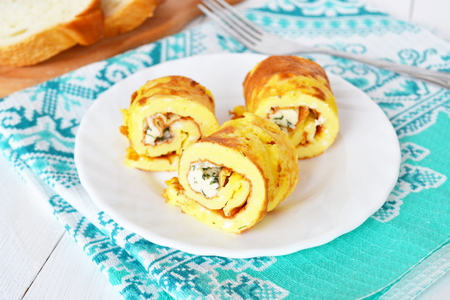 Rolls of omelette with cheese on a plate, bread, fork