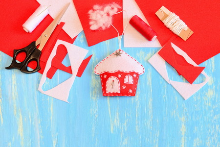 Christmas house decor sewn from red and white felt, scissors, felt sheets and scraps, needle, thread spool, filler on a blue wooden background with copy space for text. Christmas DIY concept. Top view Stock Photo
