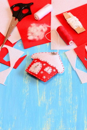 Christmas house ornament sewn from red and white felt, scissors, felt sheets and scraps, needle, thread spool on a blue wooden background with copy space for text. Easy and cheap Christmas DIY Stock Photo
