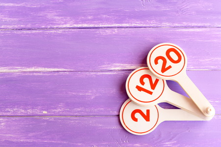 Educational toy to teach children numbers. Learning toy for kids on lilac wooden background with empty space for text. Teaching numbers to preschoolers fun Stock Photo