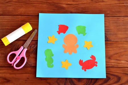 children crab: Paper card with sea animals and fishes. Creative ocean creatures crafts for kids. Paper octopus, fish, starfish, seahorse, crab project for children. Scissors, glue on a wooden table