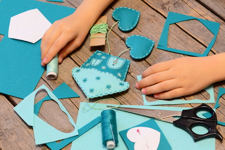 Small child made a house with hearts ornament of felt. Materials and tools for making felt ornaments. How to teach child to hand sew. Simple lesson sewing 版權商用圖片