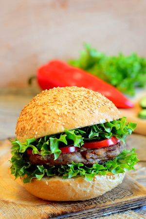Sandwich with a fried bean burger, lettuce, red bell pepper and cucumber. Wholesome sandwich on a wooden board, fresh vegetables. Simple vegan sandwich idea. Vintage style. Closeup Stock Photo