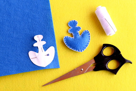 Home made anchor ornament. Blue felt anchor is sewn with white thread, needle, paper pattern pinned on a flat piece of blue felt, scissors on a yellow background. Sewing instruction for children. Step Stock Photo