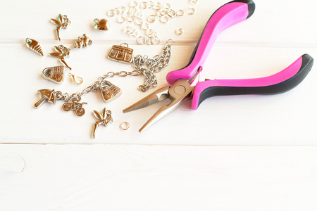 Pliers, chain, metal rings and pendants on a white wooden background. How to make yourself metal bracelet 版權商用圖片