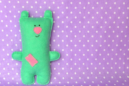 Cute green felt Teddy bear - handmade children toy. Background with copy space for text