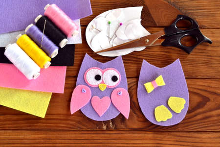Set for sewing a felt owl, paper templates, felt sheets, scissors, thread, needle, pins on a brown wooden background. Felt owl pattern. Step. Felt owl sewing tutorial. Sewing lessons for kids teaching