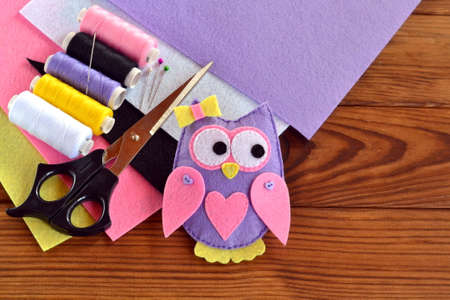 Handmade felt owl, felt sheets, scissors, thread, needle, pins on a brown wooden background. Sewing tutorial. Step. Felt owl sewing. Sewing lessons for beginners step by step