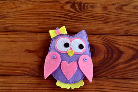 Cute handmade felt owl with bow and heart isolated on a brown wooden background. Felt ornament. Felt owl toy. Sewing lessons for kids teaching. Sewing lessons for beginners step by step. Sewing lesson