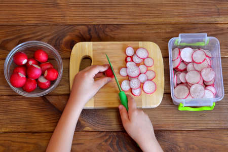 Child cuts radish for salad using kitchen knife. Children hands holding a knife and a radish. Vegetables for salad. Top view. Salad recipe for kids. Kids cooking activities at home