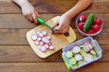 Child is preparing vegetable salad. Child holding a knife and cut a radish. Children hands holding a kitchen knife and a radish. Kids cooking activities education life skills