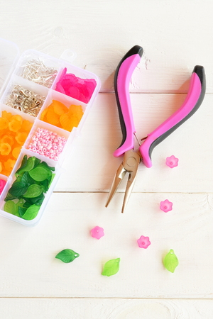 specific: Supplies and tool for creating handmade jewelry. Plastic box with assorted beads, flowers, leaves and metal rings and pins. Pliers. Close-up. Vertical photo
