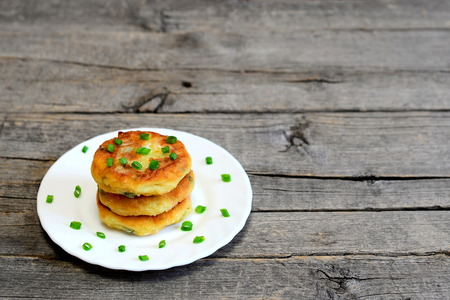 Mixed vegetable cutlets on a plate isolated on wooden background with copy space. Fried cutlets made of potatoes, green peas, carrot and green beans and garnished with fresh green onion. Veggie recipe Stock Photo