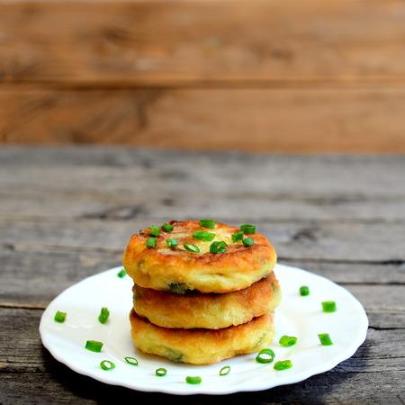 Empanadas vegetales mezcladas en una placa aislada en fondo de madera. Empanadas fritas cocinadas con papas, guisantes verdes, zanahoria y judías verdes y adornadas con cebolla verde fresca. Delicioso plato de verduras Foto de archivo