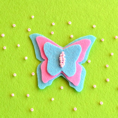 Felt butterfly on a green background, beads. Simple childrens crafts Stock Photo