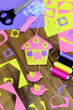 wall decor: Home wall decor. Colourful felt house decor with birds and flowers. Craft materials and tools on a wooden table. Homemade Easter wall decoration. Original holiday crafts