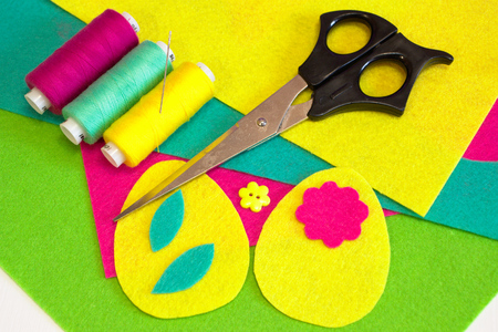Easter egg patterns set, flower sewing buttons, colored threads set, scissors, flat felt pieces. How to make Easter egg ornament. Easy sewing crafts. Step Stock Photo