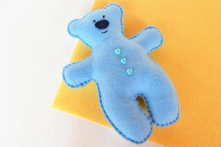 Handmade felt bear - blue felt bear on yellow background, hand-stitched toy, a craft out of felt