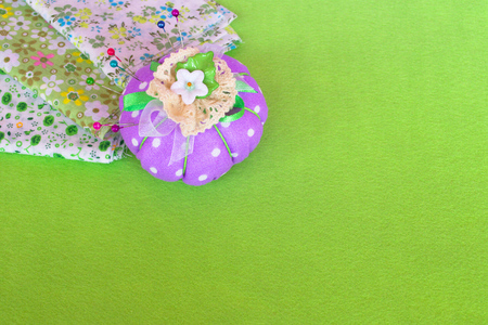 The pin cushion with pieces of cloth on the green felt