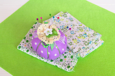 needle laces: The pin cushion with pieces of cloth on the green felt