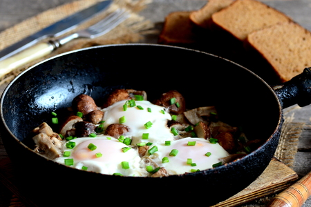 Fried eggs in pan. Eggs fried with mushrooms and green onions. Brown bread slices, fork, knife on a wooden table. Quick vegetarian breakfast recipe with eggs. Vintage style. Closeup