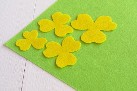 Handmade yellow felt flower sewing kit on the green felt and white wooden background