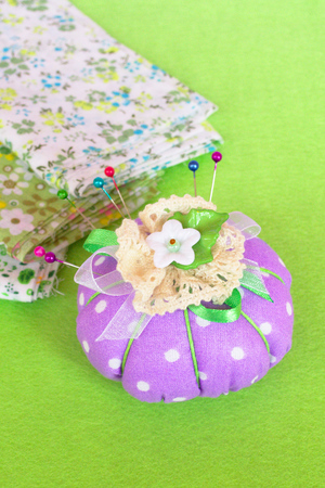 needle laces: Pin cushion with pieces of cloth on the green felt