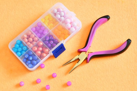Box of pliers and beads on a beige felt