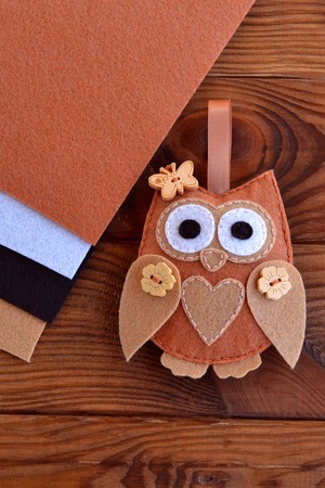Felt brown owl. Shabby chic style. Kids crafts. Felt sheets. Brown wooden table. Close-up Stock Photo