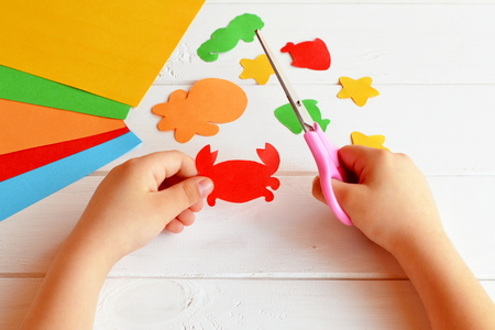 Child holds a scissors and cuts paper crab. Art lesson in kindergarten. Paper sea animals - octopus, fish, starfish, seahorse, crab. Kids crafts