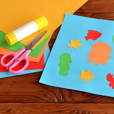 Paper applique with sea animals and fishes. Art lesson in kindergarten. Paper sea animals - octopus, fish, starfish, seahorse, crab. Kids diy. Sheets of colored paper, scissors, glue Stock Photo